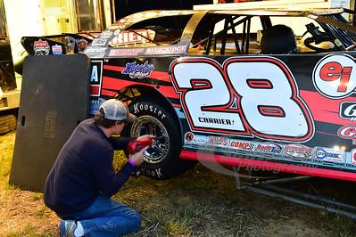 Josh McGuire tightens the lug nuts on Eddie Carrier, Jr.'s machine