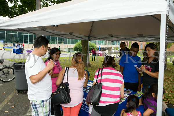 People receive information from Planned Parenthood Mid Hudson Valley at the Newburgh Enlarged City School District sponsored Back-to-School Backpack BBQ at the BOE/Library on Grand St in Newburgh on Saturday, August 23, 2014. Hudson Valley Press/CHUCK STEWART, JR.