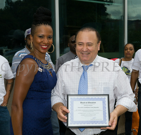 Ms. Shena Biaz presents Assemblyman Frank Skartados with an award at the Newburgh Enlarged City School District sponsored Back-to-School Backpack BBQ at the BOE/Library on Grand St in Newburgh on Saturday, August 23, 2014. Hudson Valley Press/CHUCK STEWART, JR.