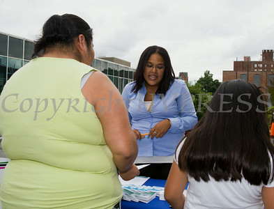 People receive information from Maternal Infant Services Network (MISN) worker Madeline Henriquez at the Newburgh Enlarged City School District sponsored Back-to-School Backpack BBQ at the BOE/Library on Grand St in Newburgh on Saturday, August 23, 2014. Hudson Valley Press/CHUCK STEWART, JR.