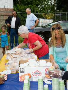 People receive free hot dogs and hamburgers at the Newburgh Enlarged City School District sponsored Back-to-School Backpack BBQ at the BOE/Library on Grand St in Newburgh on Saturday, August 23, 2014. Hudson Valley Press/CHUCK STEWART, JR.