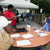 People receive information from City of Newburgh Rec Department worker Jason Szeli at the Newburgh Enlarged City School District sponsored Back-to-School Backpack BBQ at the BOE/Library on Grand St in Newburgh on Saturday, August 23, 2014. Hudson Valley Press/CHUCK STEWART, JR.