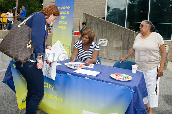 People receive information from Newburgh Enlarged City School District Adult Education Program workers Tynisa Woody and Bertha Anderson at the Newburgh Enlarged City School District sponsored Back-to-School Backpack BBQ at the BOE/Library on Grand St in Newburgh on Saturday, August 23, 2014. Hudson Valley Press/CHUCK STEWART, JR.