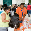 People receive information from WellCare worker Brian Rodriguez at the Newburgh Enlarged City School District sponsored Back-to-School Backpack BBQ at the BOE/Library on Grand St in Newburgh on Saturday, August 23, 2014. Hudson Valley Press/CHUCK STEWART, JR.