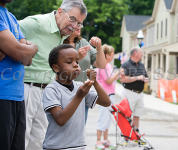 A child blows bubles at the conclusion of Habitat for Humanity of Greater Newburgh's dedication of the Spearman and Martinez homes on East Parmenter St. in the City of Newburgh on Saturday, June 14, 2014 to complete the week long Builders Blitz. Hudson Valley Press/CHUCK STEWART, JR.