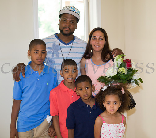The Spearman family poses for a picture in the living room front of their new home following Habitat for Humanity of Greater Newburgh's dedication on East Parmenter St. in the City of Newburgh on Saturday, June 14, 2014 to complete the week long Builders Blitz. Hudson Valley Press/CHUCK STEWART, JR.