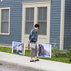 A woman looks at photos depicting what East Parmenter Street looked like in 2007 prior to Habitat for Humanity of Greater Newburgh dedicated the Spearman and Martinez homes on East Parmenter St. in the City of Newburgh on Saturday, June 14, 2014 to complete the week long Builders Blitz. Hudson Valley Press/CHUCK STEWART, JR.