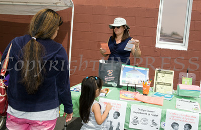 Marisol Rivera-Torres of the Orange County Department of Health hands out information at Hudson Health Plan's free Bicycle Safety Rodeo on Saturday, August 16, 2014, at Second Baptist Church in Middletown, NY. Hudson Valley Press/CHUCK STEWART, JR.