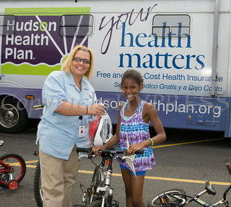 Marisol Guzman of Hudson Health Plan gives a bike and helmet to Jazmine during the free Bicycle Safety Rodeo on Saturday, August 16, 2014, at Second Baptist Church in Middletown, NY. Hudson Valley Press/CHUCK STEWART, JR.