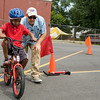 Seven-year-old Mason tackles the bike safety course under the direction of Warren Mastrogiovanni during Hudson Health Plan's free Bicycle Safety Rodeo on Saturday, August 16, 2014, at Second Baptist Church in Middletown, NY. Hudson Valley Press/CHUCK STEWART, JR.
