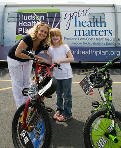 Rosina Tezgeldi of Hudson Health Plan gives eight-year-old Marianne a bike and helmet during a free Bicycle Safety Rodeo on Saturday, August 16, 2014, at Second Baptist Church in Middletown, NY. Hudson Valley Press/CHUCK STEWART, JR.