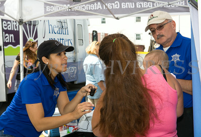 Barbara Martinez and Robert Rushing of the Orange County Sheriff's Office were on-site for parents who wanted to make IDs for their children during Hudson Health Plan's free Bicycle Safety Rodeo on Saturday, August 16, 2014, at Second Baptist Church in Middletown, NY. Hudson Valley Press/CHUCK STEWART, JR.