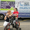 Rosina Tezgeldi of Hudson Health Plan gives five-year-old Ruby a bike and helmet during a free Bicycle Safety Rodeo on Saturday, August 16, 2014, at Second Baptist Church in Middletown, NY. Hudson Valley Press/CHUCK STEWART, JR.