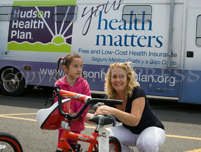 Rosina Tezgeldi of Hudson Health Plan gives four-year-old Elsie a bike and helmet during a free Bicycle Safety Rodeo on Saturday, August 16, 2014, at Second Baptist Church in Middletown, NY. Hudson Valley Press/CHUCK STEWART, JR.