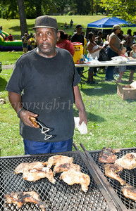 Franklin Culberth cooks up chicken on the grill for members of the community who gathered in Downing Park as part of the I'm So Newburgh Stop the Violence event on Saturday, August 23, 2014. Hudson Valley Press/CHUCK STEWART, JR.