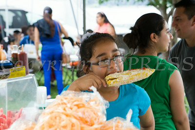 Kimberlin Juarez enjoys corn on the cob with cheese, ketchup, spicy powder and mayo during the sixth annual La Guelaguetza which was held in Waryas Park in Poughkeepsie, NY on Sunday, August 3, 2014. Hudson Valley Press/CHUCK STEWART, JR.