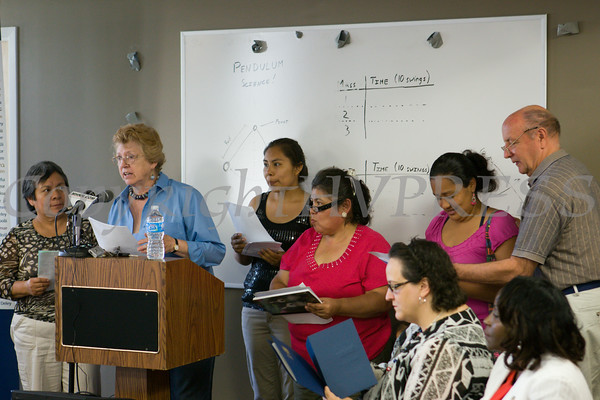 Dr. Karen Eberle-McCarthy, at podium, leads a song during the U.S. Citizenship and Immigration Services Customer Service Center open house at the Newburgh Armory Unity Center on Saturday, July 12, 2014 in Newburgh, NY. Hudson Valley Press/CHUCK STEWART, JR.