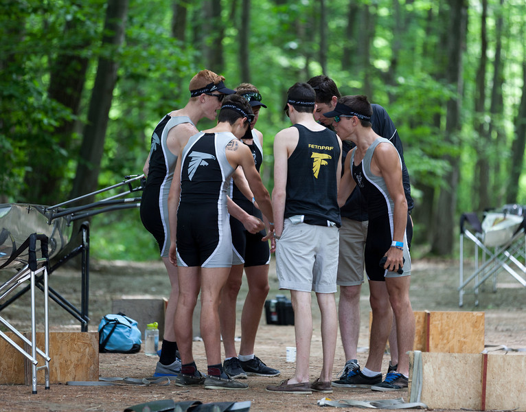 Boys 1V with coach Marcus in pre-race huddle
