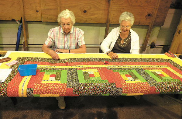 Debbie Wachter/NEWS<br /> Donna Nagel, a member of East New Castle Grange,  left, and Eleanor Boyles, of Mahoning Valley Grange, stitch a quilt that will be auctioned later in the week at the fair.