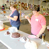 Long-time baked goods judge Barb Benson, right, and fellow judge Kristen Trask sample the entries in the chocolate cake contest Saturday afternoon. — Mitchel Olszak