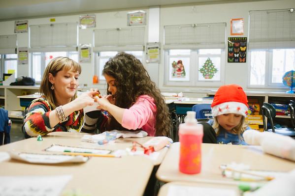 JOED VIERA/STAFF PHOTOGRAPHER-Lockport, NY-Ericka Milczarski helps Charles Upson Elemantary 3rd grader Mariah Cornielle stuff a stocking in class.Thursday, December 11, 2014