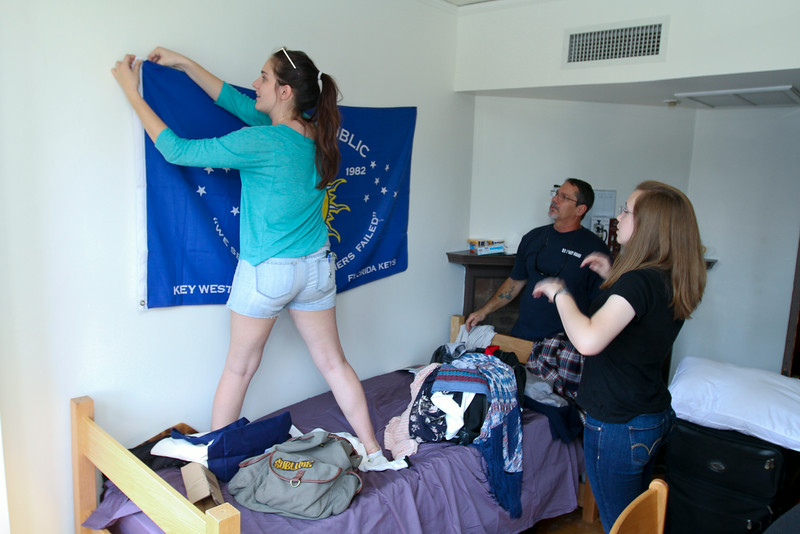 laney Harrington '18 from Miami, FL, hangs a banner in her room as roommate Sophia Gehrmann '18 from Urbana, IL, and dad William Harrington watch.<br /> Photo Credit: Paola Nogueras