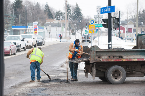 140204 3A ENT JOED VIERA/STAFF PHOTOGRAPHER Lockport ,NY- Paul Chaffin grabs gravel from a truck while Raymond Ladrich patches up a pot hole on the corner of East Ave. and South Transit Road on February 4th, 2014.