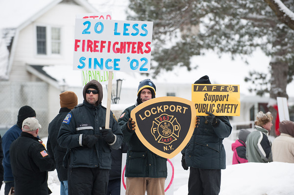 140211 PROTEST  JOED VIERA/STAFF PHOTOGRAPHER-Lockport, NY-Lockport Firefighters hold up protest signs in front of the Lockport Country Club during Mayor Tucker's state of the city address on Tuesday February 11th, 2014.