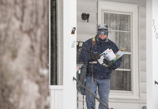 140102 Winter Enterprise JOED VIERA/STAFF PHOTOGRAPHER Lockport, NY-A letter carrier delivers mail in two digit temperature during the snowfall Thursday Jan 2nd, 2013.