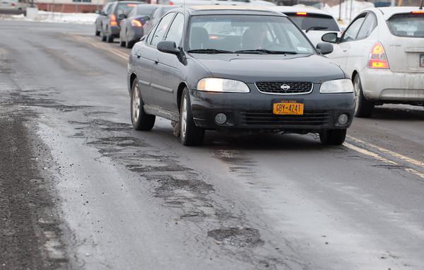 140131 Potholes JOED VIERA/STAFF PHOTOGRAPHER Lockport ,NY- A car avoids a pothole on Old Beattie Ave on January 31st, 2014.