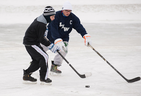 140108 Hockey JOED VIERA/STAFF PHOTOGRAPHER Lockport,NY-David Poole attempts to relieve Donnie Mullen of the puck during a hockey game on a patch of ice they made into a makeshift hockey rink in front of the Kenan Center on Wednesday.