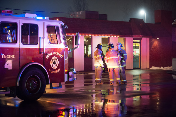 131220 Masterpiece fire  JOED VIERA/STAFF PHOTOGRAPHER Lockport, NY-First South Lockport volunteer firefighters stand outside of Masterpiece Pizza after putting out a grease fire at the establishment on Friday Dec 20th, 2013.