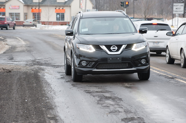 140131 Potholes JOED VIERA/STAFF PHOTOGRAPHER Lockport ,NY- A car runs over potholes on Old Beattie Ave on January 31st, 2014.