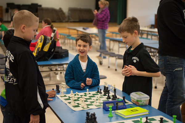 131230 Upton Chess JOED VIERA/STAFF PHOTOGRAPHER Lockport, NY-Upson Elementary's JonLuke Pencille(center) laughs as he watches a chess match between two Pioneer Elementary students at the Upson's beginners chess championship on Monday Dec 30th, 2013. Pencille won the championship in the K-1 division.