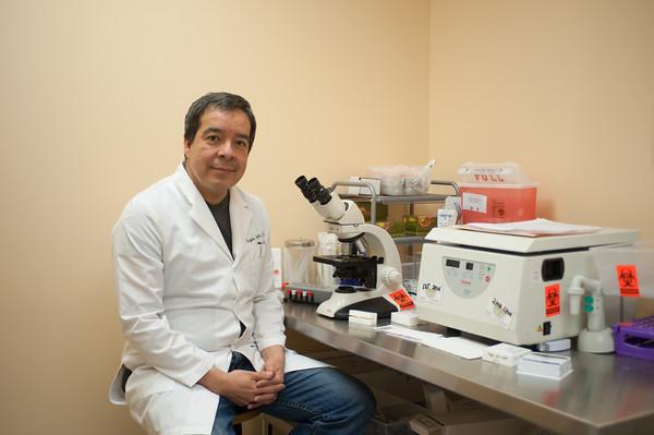 140124 Arroyo JOED VIERA/STAFF PHOTOGRAPHER Lockport,NY-Dr. Armando Arroyo sits next to a microscope on Friday, January 24th.