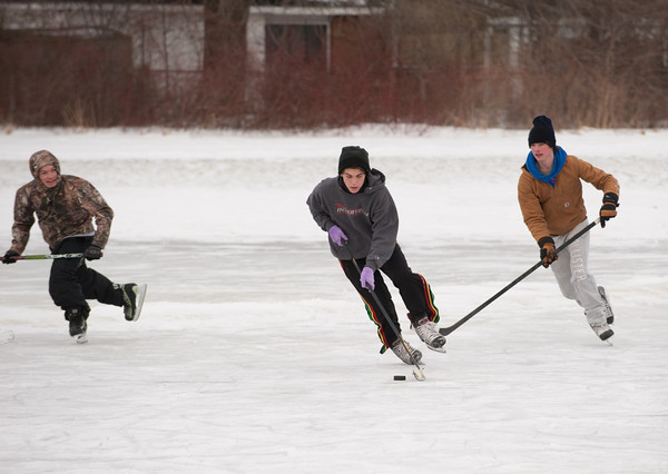 140108 Hockey JOED VIERA/STAFF PHOTOGRAPHER Lockport,NY- David Craddock(left) and Dante Kinney(right) chase after Matt Gagliardy(center) on a patch of ice they made into a makeshift hockey rink in front of the Kenan Center on Wednesday.