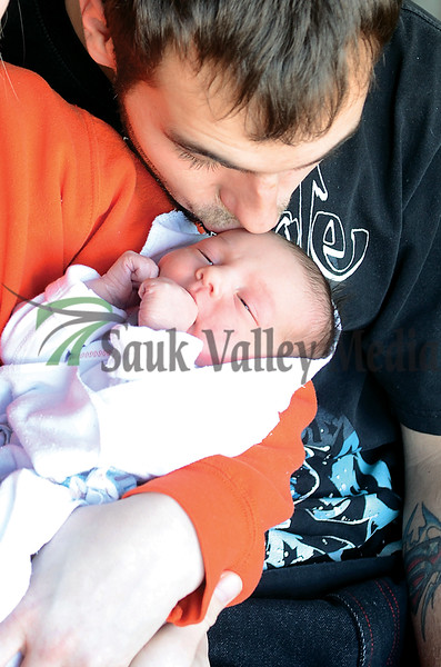 Adam Owens kisses his new daughter Riley Adilynn who came into the world January 1st at KSB in Dixon.