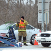 A firefighter works at the scene of a car versus semi-truck accident on Route 88 Thurdsday morning. The car got tangled in the rig's empty car transporter.