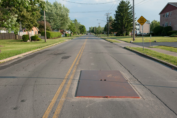 140702 JOED VIERA/STAFF PHOTOGRAPHER-Lockport, NY-A steel plate covers a sinkhole on Davison Road on July 2, 2014.