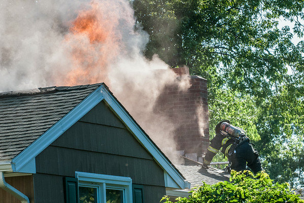 14010 JOED VIERA/STAFF PHOTOGRAPHER-Lockport, NY-A City of Lockport Firefighters attempts to put out a blaze on the roof of a house on Hoover Parkway on Thursday, July 10th.