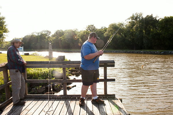 140702 JOED VIERA/STAFF PHOTOGRAPHER-Lockport, NY-Warren Matthews(left) watches as Aaron Woods reels in a Bullhead during the Erie Canal Fishing Derby on July 2, 2014.