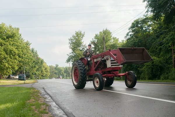 140430 JOED VIERA/STAFF PHOTOGRAPHER-Lockport, NY-A man drives his tractor to the Niagara County Fair on Wednesday July 30th.