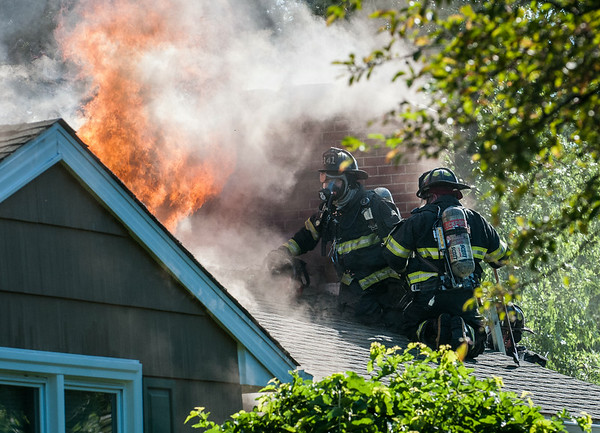 14010 JOED VIERA/STAFF PHOTOGRAPHER-Lockport, NY-City of Lockport Firefighters attempt to put out a blaze on the roof of a house on Hoover Parkway on Thursday, July 10th.