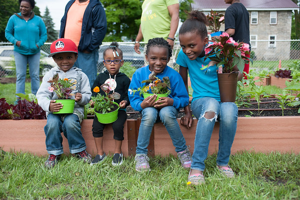 140614 Garden JOED VIERA/STAFF PHOTOGRAPHER-Lockport, NY-Desean( no last name given) 2, Salissa Davis 2, Jailyn Gillon 7 and Sian Powell 11 hold flower pots at the new community garden on the corner of Ontario St. and Hawley St. June 14, 2014