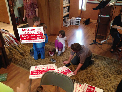 Kids Putting Together Russian Festival Signs