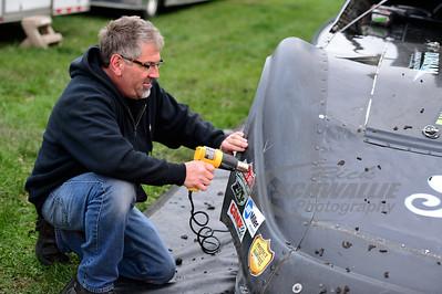 Tony Wiggans applies decals to the nose of Scott Bloomquist's race car