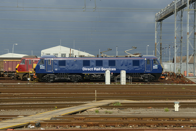 26 March 2014 :: Photographed from a passing train (so apologies about the 2 grey boxes but at least the rest was clear!), the DRS blue liveried class 90, No. 90034 stabled at Willesden.  This locomotive has been prepared to work on the Virgin Trains loco hauled services