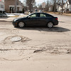 140326 Road Damage JOED VIERA/STAFF PHOTOGRAPHER-Lockport, NY- A car drives through potholes on North Transit St. Mar.26, 2014.