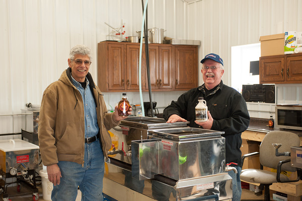 140319 Maple JOED VIERA/STAFF PHOTOGRAPHER-Cambria, NY- Rich Goodman and Tony Gaeta hold up maple syrup at thier cook room on Wednesday, Mar. 19th, 2014.
