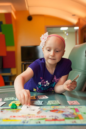 140425 Skyla JOED VIERA/STAFF PHOTOGRAPHER-Buffalo, NY-Skyla Dennis picks up a chance card while playing a game of Monopoly Jr. in the game room of Roswell Cancer Institute. April 23, 2014.